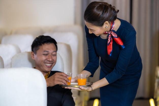 승무원 서비스, 비행기에서 승객에게 음료를 제공하는 아시아 여성 승무원, 기내 승무원 또는 비행기에서 일하는 여주인.