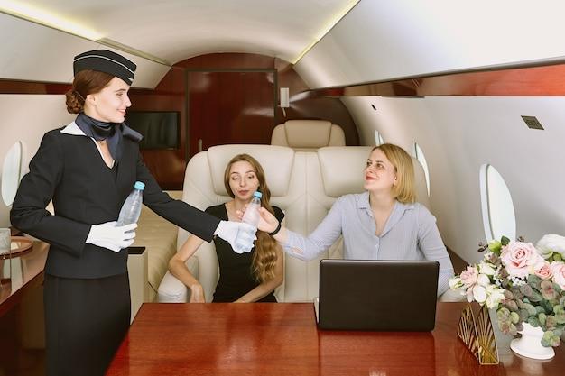 Flight attendant serving passengers inside plane.