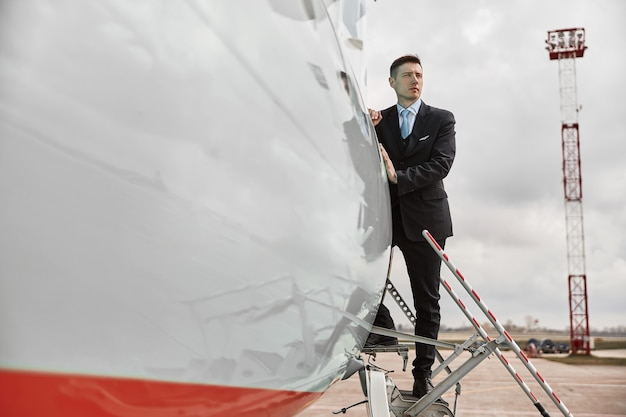 Flight attendant standing on ladder of airplane jet. modern passenger plane. concentrated multiracial man wear uniform. sunny daytime. civil commercial aviation. air travel concept