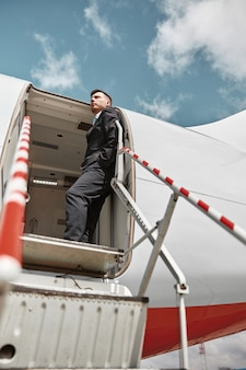 Flight attendant standing on private airplane jet with ladder. modern passenger plane. bottom view of serious multiracial man wear uniform. sunny daytime. civil commercial aviation. air travel concept