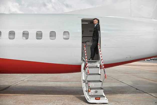 Flight attendant standing on private airplane jet with ladder. modern passenger plane. serious multiracial man wear uniform. sunny daytime. civil commercial aviation. air travel concept