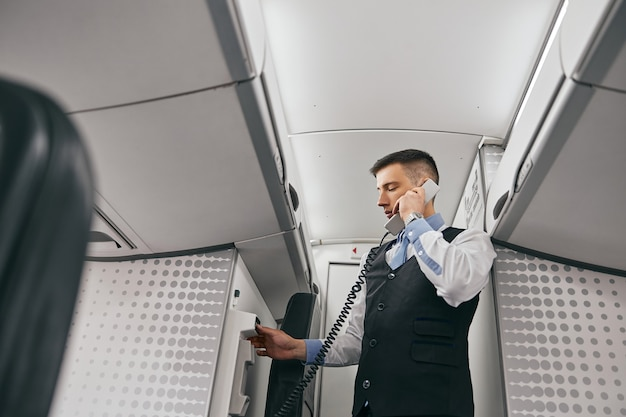 Flight attendant talk on board phone in passenger cabin of airplane jet. modern plane interior. bottom view of mixed race man wear uniform. civil commercial aviation. air journey concept