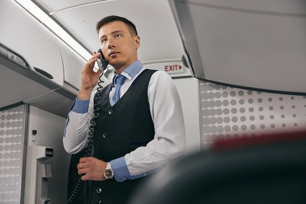 Flight attendant talk on board phone in passenger cabin of airplane jet. modern plane interior. bottom view of multiracial man wear uniform. civil commercial aviation. air journey concept