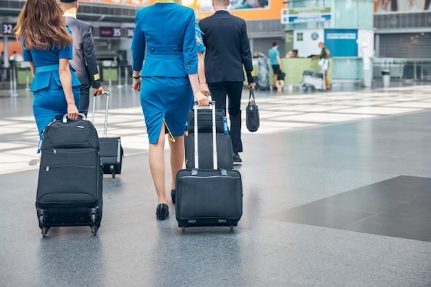Стюардессы в синей форме и пилоты с сумками для багажа на тележке, идущие в терминале аэропорта
