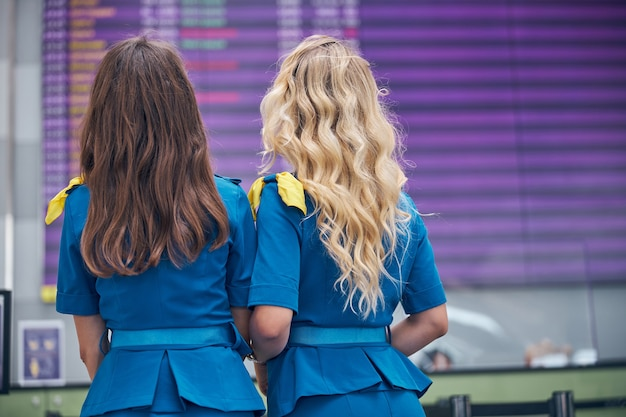 Flight attendants with beautiful hair checking time of plane arrival in airport terminal