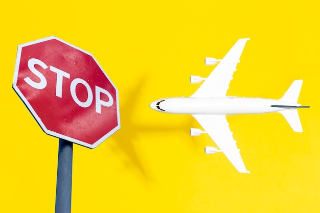 Запрет на полеты и закрытые границы для туристов и путешественников. концептуальный самолет nofly zone в полете со знаком остановки фото высокого качества