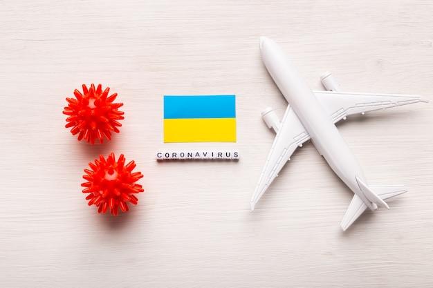 Запрет на полеты и закрытые границы для туристов и путешественников с коронавирусом ковид-19. самолет и флаг украины на белом фоне. коронавирус пандемия.