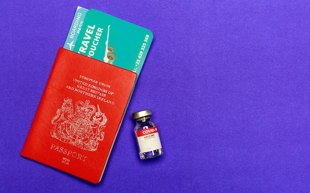 Flight boarding pass, red passport, visa beside world recommended covid-19 vaccine glass for global traveler and foreigner to qualify aboard permission as disease outbreak prevention.