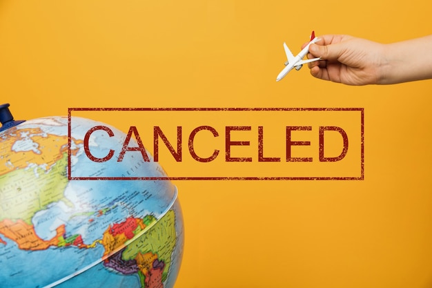 항공편이 취소되었습니다. 여객기의 입상을 들고 차일 손. 지구에 비행하는 비행기.
