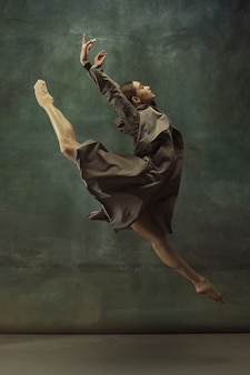 In flight. graceful classic ballerina dancing, posing isolated on dark studio background. stylish trench coat. grace, movement, action and motion concept. looks weightless, flexible. fashionable.