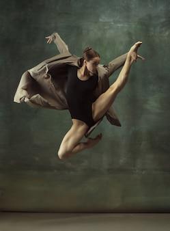In flight. graceful classic ballerina dancing, posing isolated on dark studio wall