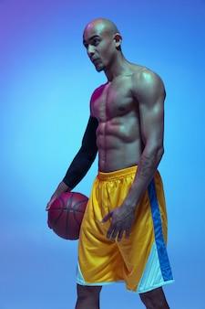 フライト。青い壁にネオンの光の中で動きとアクションでハンサムなアフリカ系アメリカ人の男性のバスケットボール選手。