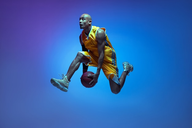 Flight. handsome african-american male basketball player in motion and action in neon light on blue wall.