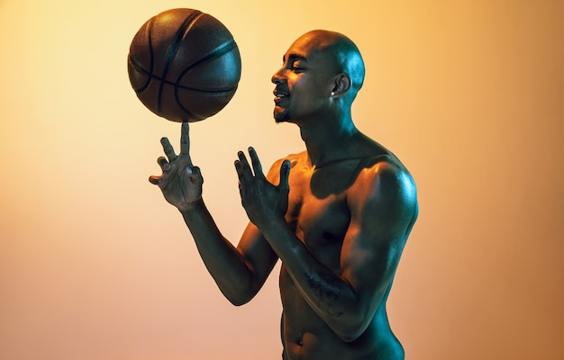 Flight. handsome african-american male basketball player in motion and action in neon light on orange wall.