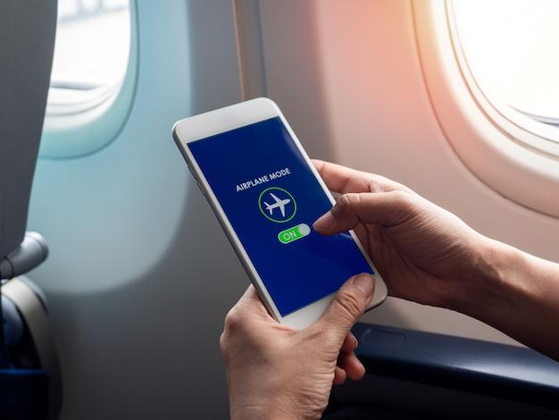 Концепция режима полета. рука держа белый смартфон и включил режим самолета на экране возле окна на самолете.