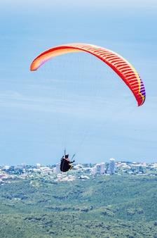 海岸上空のパラグライダーアスリートの飛行