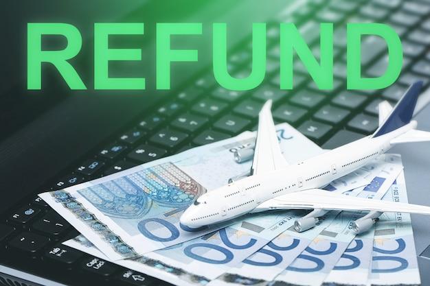 航空券の払い戻し。ノートパソコンのキーボード上の小さなおもちゃの飛行機とユーロ紙幣