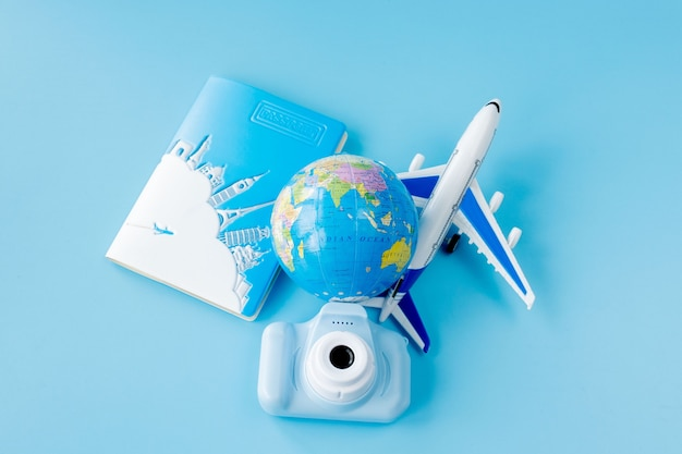 Flight tickets with passports, camera, model of airplane and globe on blue background. summer or vacation concept. copy space.