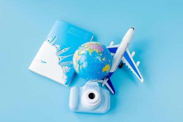 パスポート、カメラ、飛行機のモデル、青い背景の地球儀の航空券。夏や休暇のコンセプト。スペースをコピーします。