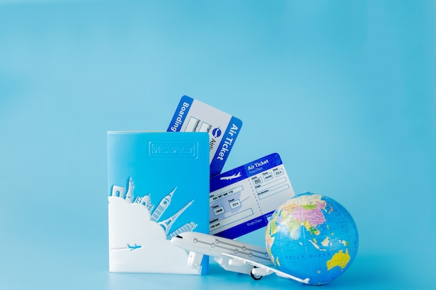 Flight tickets with passports, model of airplane and globe. summer or vacation concept. copy space.
