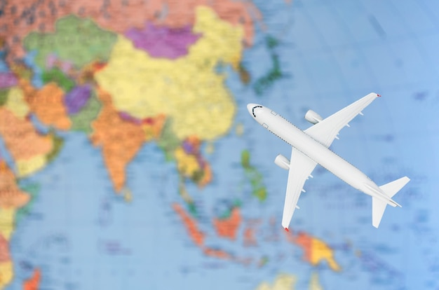 飛行機の地図による旅行のアジアへの飛行の象徴的なイメージ。