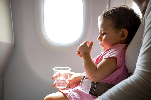 Flight with infant toddler sits on mom lap fastened with a special belt in airplane before porthole