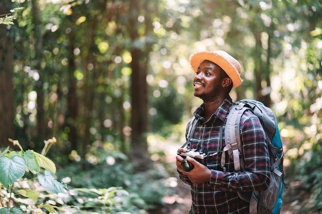 Человек путешественника держа камеру flim в зеленом лесе