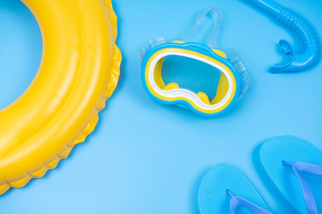 Flip-flop and snorkeling mask with colorful ring floating yellow