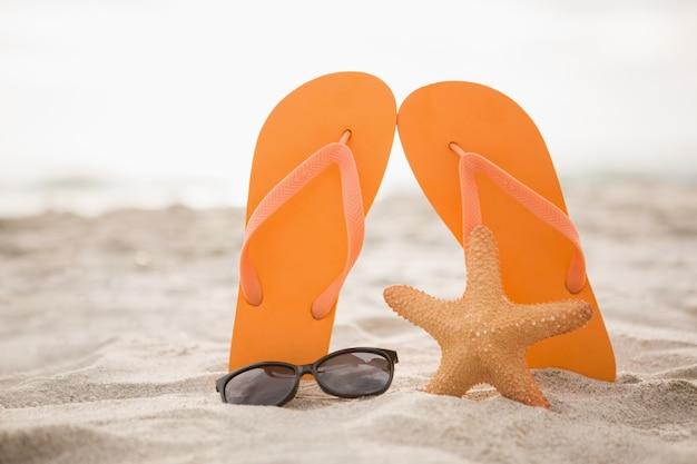 Occhiali da sole, flip flop e stelle marine nella sabbia