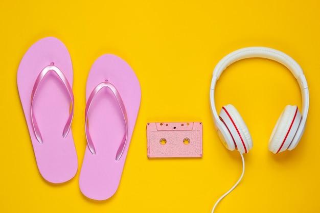 노란색 배경에 헤드폰 및 오디오 카세트와 플립 플롭. 여름철 휴식. 여름 방학. 아름다움과 패션.