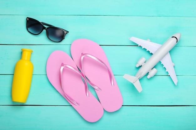 Flip flops, airplane, sunglasses, bottle of sunblock on a blue wooden