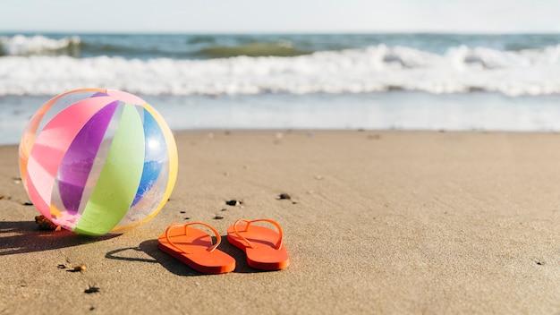 Флип-флоп и надувной шар в песке на пляже