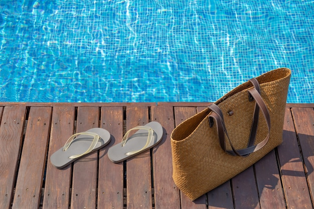 Flip flops and beach bag on wooden deck next to swimming pool.