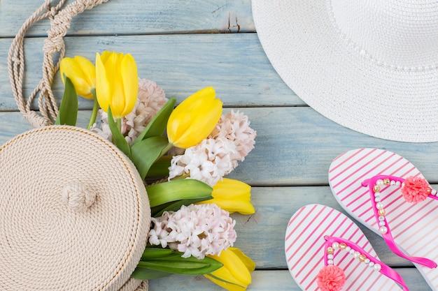 Шлепанцы, пляжная шляпа, плетеная круглая сумка и букет тюльпанов и гиацинтов