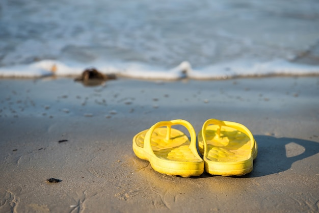 Flip flops on beach at sunny day