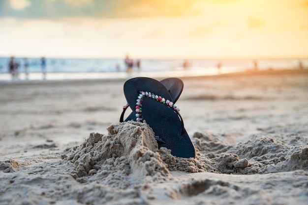 Flip flops on beach with sandy beach sunset and ocean sea background