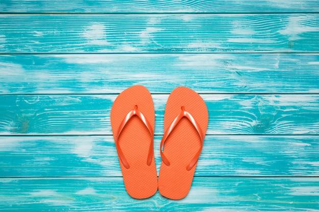 Flip flops on blue wooden floor.