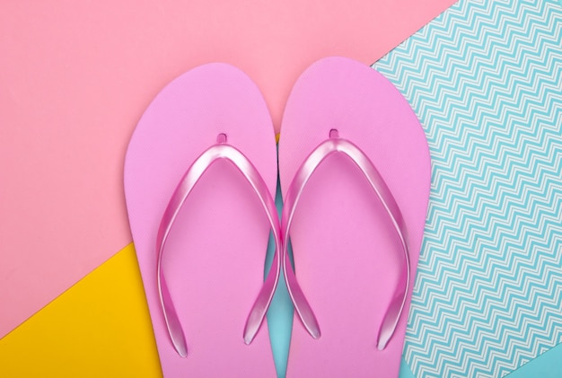 Flip flops on colored pastel background. top view