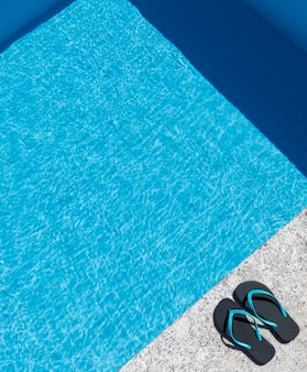 Flip flops on the edge of a pool. copy space. top view.
