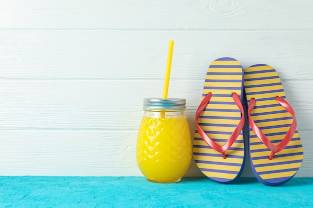 Flip flops and glass jar with fresh juice on color table against white wooden background, space for text. summer vacation concept