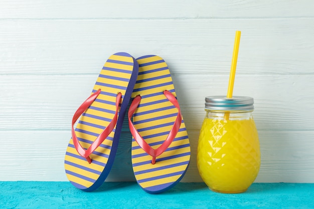 Flip flops and glass jar with fresh juice on color table against white wooden wall, space for text. summer vacation concept