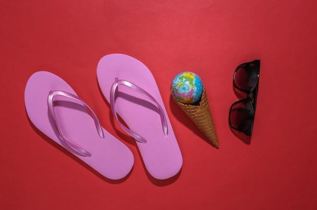 플립 플롭, 글로브가 있는 아이스크림 와플 콘, 빨간색 배경에 선글라스.