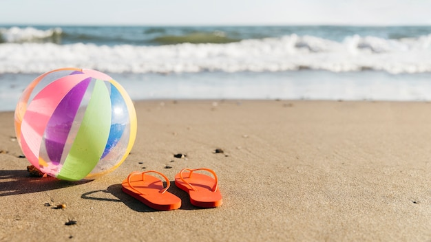 Flip flops and inflatable ball in the sand at the beach