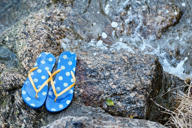 Flip-flops left on a rock by the water, summer time concept