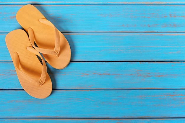 Flip flops on old weathered blue beach wood