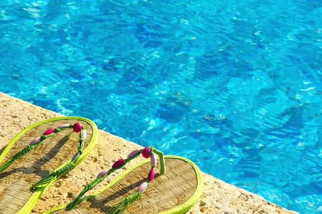 スイミングプールの横のプラットフォームでビーチサンダル