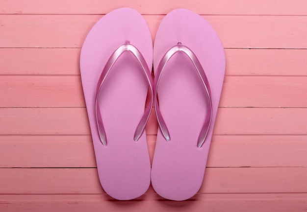 Flip flops on a pink wooden