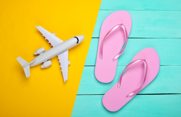 Flip flops and plane on a yellow, blue wooden, travel