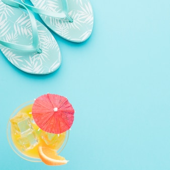 Flip-flops and refreshing cocktail on colored background