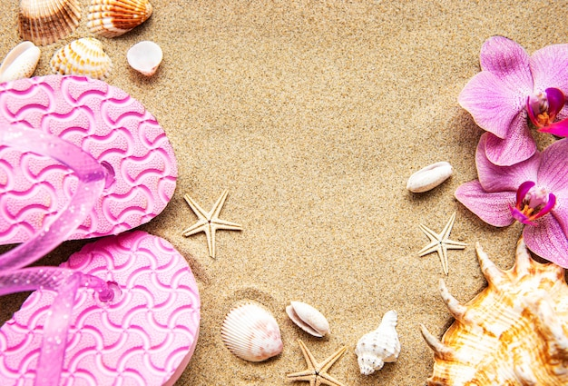 Flip flops in the sand with starfish and orchid flowers